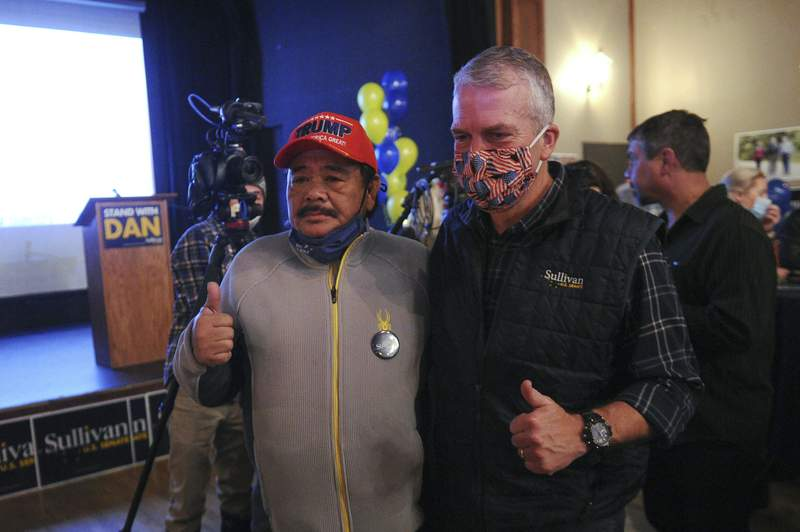 Sen. Dan Sullivan, right front, R-Alaska, poses for a photograph with supporter Rolando Torralba at a campaign party Tuesday, Nov. 3, 2020, in Anchorage, Alaska. (AP Photo/Michael Dinneen)