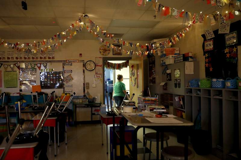 "Cherye Graves, a 4th grade English language arts teacher at Eastside Elementary in Clinton, Miss., walks out of her desolate classroom as students are forced to stay home during the coronavirus outbreak, Monday, March 23, 2020, in Clinton, Miss. Graves' room is decked out with lights and streams of ribbons in an effort she says to promote a fun learning environment for her students. ""The main part of this is missing. The reason why we come is not here. It is sad. With the children gone, this means nothing. This adds, but the heart isn't here. Hopefully we'll be able to finish the school year with warm bodies in the classroom."" (AP Photo/Julio Cortez)"
