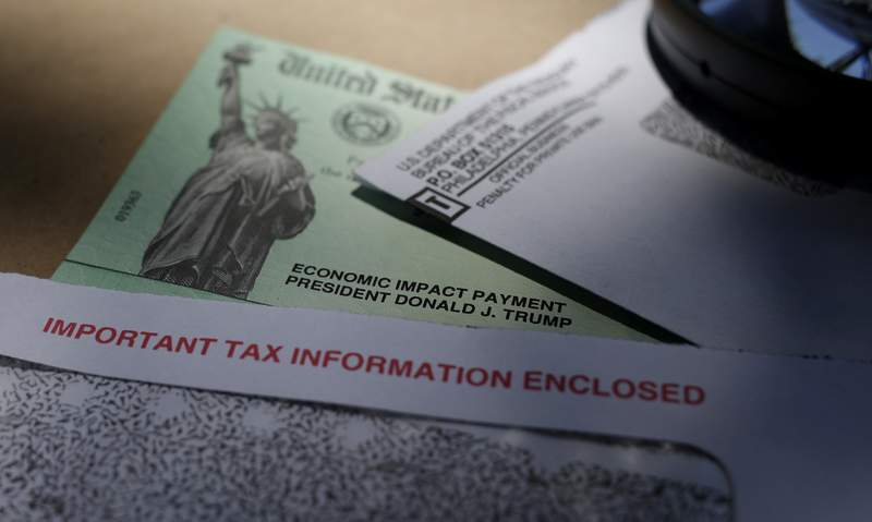 FILE - In this April 23, 2020, file photo, President Donald Trump's name is seen on a stimulus check issued by the IRS to help combat the adverse economic effects of the COVID-19 outbreak, in San Antonio. A number of taxpayers who use tax preparation services, such as H&R Block and TurboTax, say their second relief payments were sent to the incorrect bank account. The IRS and the Treasury Department began issuing the Economic Impact Payments last week of Jan. 1, 2021.   (AP Photo/Eric Gay, File)