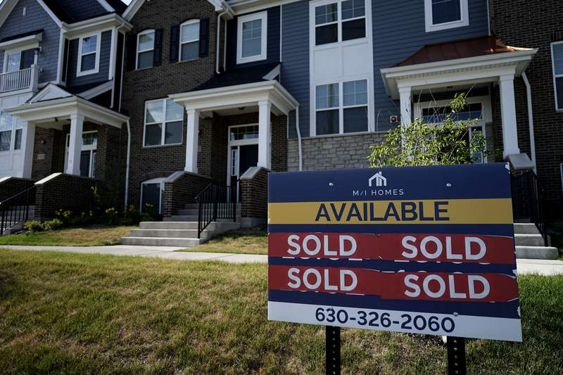An advertising sign for building land stands in front of a new home construction site in Northbrook, Ill., Wednesday, June 23, 2021.  More Americans signed contracts to buy homes in May, a surprising rebound after months of cooling in the housing market, where lack of inventory has pushed prices to record levels.    (AP Photo/Nam Y. Huh)