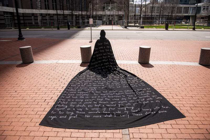 An artist who goes by Liney kneels wearing a cape outside the Hennepin County Government Center as the trial of Derek Chauvin goes on inside, on April 14, 2021 in Minneapolis. The artist came to Minnesota on Sunday to demonstrate during the trial.