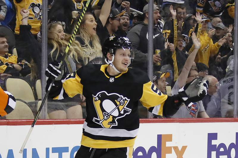 "FILE - In this Oct. 16, 2019, file photo, Pittsburgh Penguins' Jake Guentzel celebrates after scoring during the second period of an NHL hockey game against the Colorado Avalanche in Pittsburgh. Guentzel feared his season was over thanks to a shoulder injury in December. The ""pause"" caused by the pandemic has given him renewed optimism that he will be ready when the playoffs hopefully being this summer. (AP Photo/Gene J. Puskar, File)"