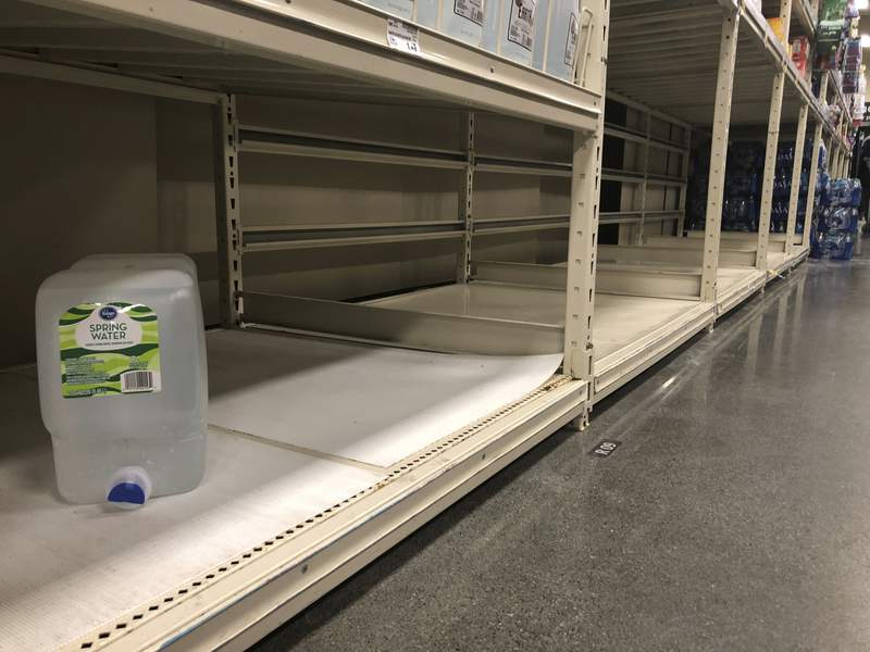 A lone container of water sits on otherwise empty shelving at a grocery store in Anchorage, Alaska, Sunday, March 1, 2020. The new coronavirus keeps turning up in more places and health experts say it's wise to prepare for wider spread. People shouldn't panic or hoard large amounts of supplies, they stress, but some common-sense steps that are useful for any emergency or disaster such as severe weather can help get your home and family ready in case you need to hunker down. (AP Photo/Mark Thiessen)