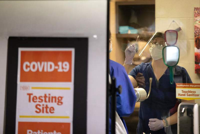 A nurse demonstrates to a student how to self-administer a COVID-19 test at a testing location at the University of Texas at Austin. (Credit: Miguel Gutierrez Jr./The Texas Tribune)