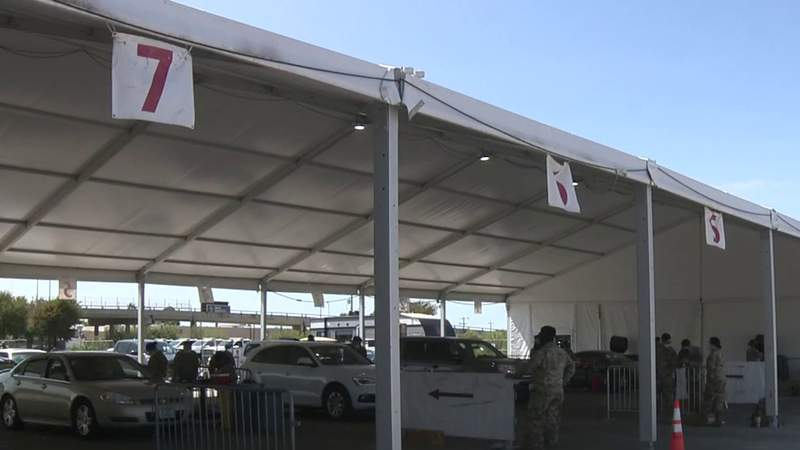 Residents line up for COVID-19 booster shots at the Alamodome parking lot