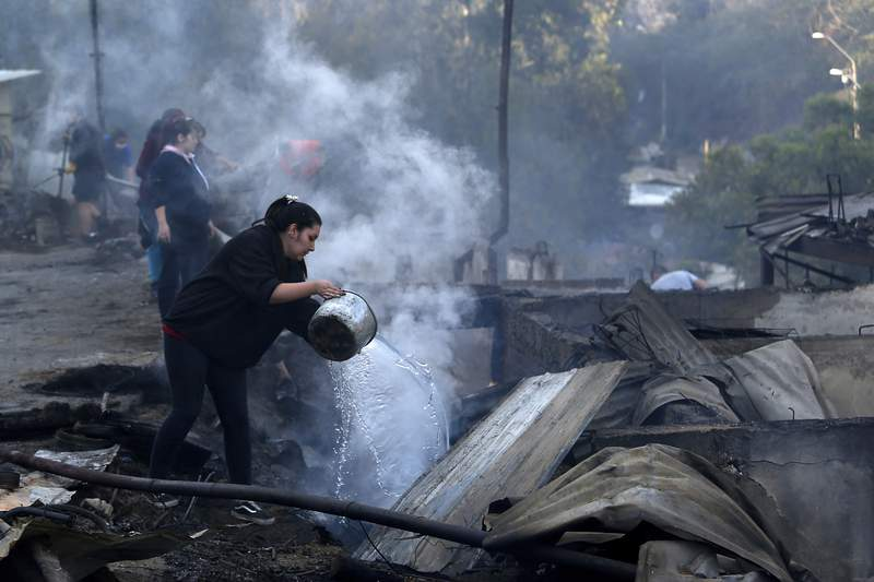 Residents spray water over remains of their homes after a wildfire damaged dozens of houses on the outskirts of Valparaiso, Chile, Wednesday, Dec. 25, 2019. The federal government in Chile declared an alert Tuesday over a wildfire that had damaged dozens of homes on the outskirts of the port city.  (AP Photo/Raul Zamora/Aton Chile via AP)