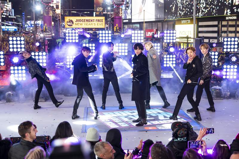 """FILE - Members of BTS perform at the Times Square New Year's Eve celebration in New York on Dec. 31, 2019. The K-pop band is nominated for a Grammy Award for best pop duo/group performance with Dynamite,"""" their first song to hit the No. 1 spot on the Billboard Hot 100 chart. (Photo by Ben Hider/Invision/AP, File)"""