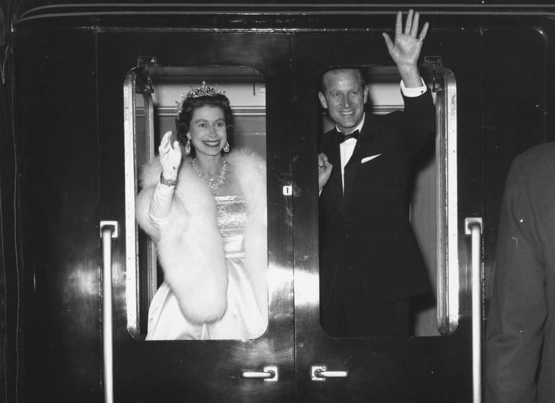 "Queen Elizabeth II and Prince Philip, the Duke of Edinburgh, wave as they leave Liverpool after attending an ice show, ""Snow White And The Seven Dwarfs"" on May 25, 1961."