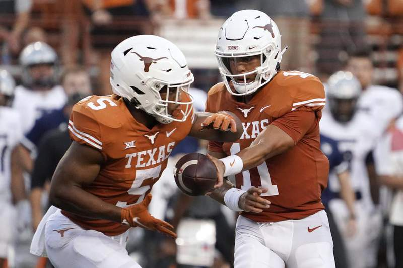 Texas quarterback Casey Thompson (11) hands the ball off to Bijan Robinson (5) during the first half of the team's NCAA college football game against Rice on Saturday, Sept. 18, 2021, in Austin, Texas.