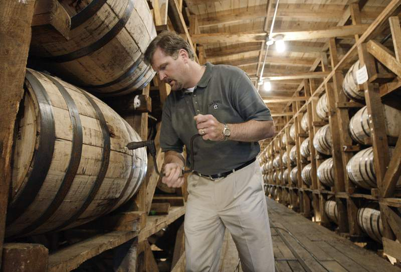 FILE  In this May 20, 2009, file photo, Jeff Arnett, the master distiller at the Jack Daniel Distillery in Lynchburg, Tenn., drills a hole in a barrel of whiskey in one of the aging houses at the distillery. The former top distiller at Jack Daniel's announced on Tuesday, April 20, 2021, that he and several partners are setting up shop for a new whiskey distillery near the Great Smoky Mountains in Tennessee. (AP Photo/Mark Humphrey, File)