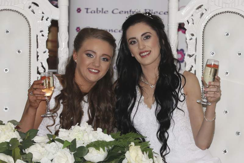 Robyn Peoples, left, 26, and Sharni Edwards, 27, pose together after becoming the first same sex couple to marry in Northern Ireland, in Carrickfergus, Northern Ireland, Tuesday Feb. 11, 2020. Two women tied the knot Tuesday in Northern Irelands first same-sex wedding, after the region became the last part of the United Kingdom to legalize gay marriage. (Liam McBurney/PA via AP)
