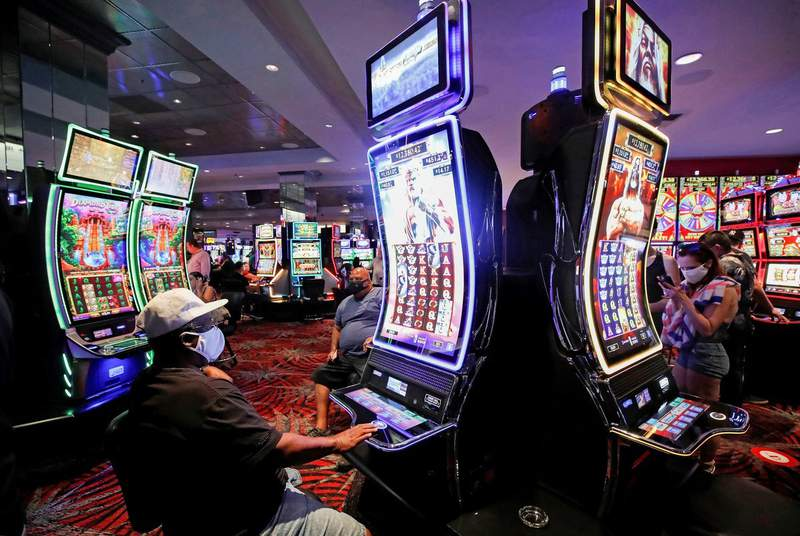 Gamblers play slot machines during the reopening of The D hotel-casino, closed by the state since March 18, 2020, as part of steps to slow the spread of COVID-19, in downtown Las Vegas, Nevada, on June 4, 2020.