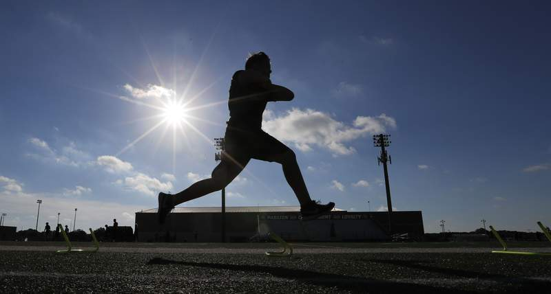 FILE - A student athlete runs a drill during a strength and conditioning camp at Arlington Martin High School Thursday, June 18, 2020, in Arlington, Texas. Texas will play high school football this fall, but some of it will be delayed, fans will be limited and masks will be required as the state fights a surge in new coronavirus cases, hospitalizations and fatalities. The University Interscholastic League on Tuesday, July 21, 2020 released its guidelines for Texas public high school fall sports, pushing back the start of the football and volleyball seasons for the largest schools by one month into late September and extending the football championships for those schools into January. (AP Photo/LM Otero, file)