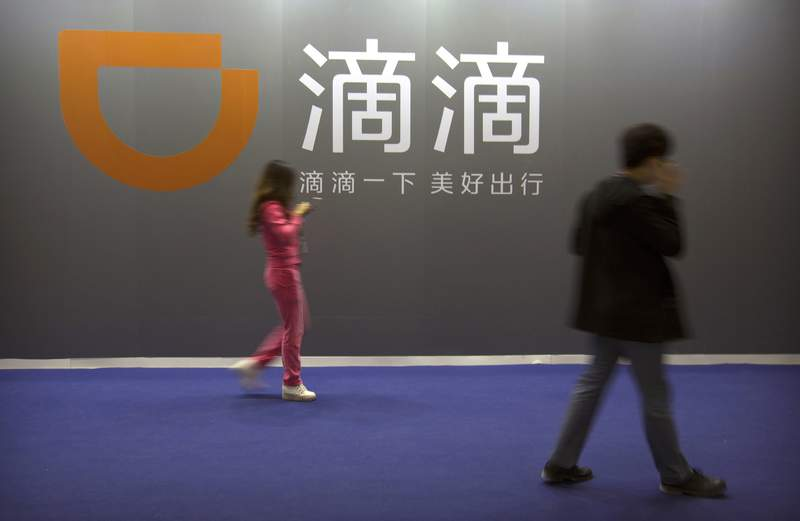 FILE - In this April 27, 2017, file photo, visitors walk past a sign for Chinese ride-hailing service Didi Chuxing at the Global Mobile Internet Conference (GMIC) in Beijing. Chinese ride-hailing service Didi says it lost $5.5 billion over the past three years ahead of its U.S. stock market debut Wednesday, June 30, 2021, but it's highlighting its global reach and investments in developing electric and self-driving cars. (AP Photo/Mark Schiefelbein,File)