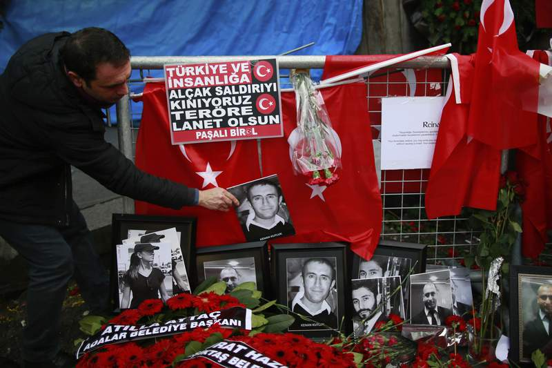 FILE - In this Wednesday, Jan. 4, 2017 file photo, a man adjusts a victim's photograph displayed with floral tributes and Turkish flags, outside the Reina night club following the New Year's day attack, in Istanbul. A Turkish court has on Monday, Sep. 7, 2020 sentenced an Islamic State militant to life in prison over the New Years Eve attack on a nightclub in Istanbul that left 39 people dead in 2017. Albulkadir Masharipov of Uzbekistan was charged with membership in a terror group, murder and attempting to overthrow the constitutional order, among other charges. (AP Photo/Emrah Gurel, file)
