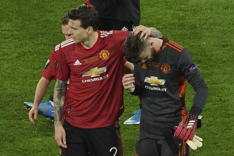 Manchester United's goalkeeper David de Gea, right, its consoled by Victor Lindelof after de Gea missed a penalty giving victory to Villarreal during the Europa League final soccer match between Manchester United and Villarreal in Gdansk, Poland, Wednesday May 26, 2021. (Aleksandra Szmigiel, Pool via AP)