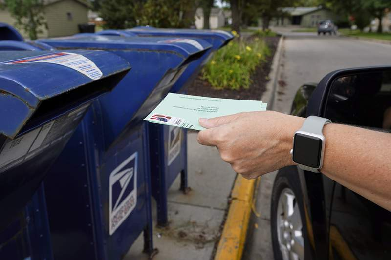 FILE - In this Tuesday, Aug. 18, 2020, file photo, a person drops applications for mail-in-ballots into a mail box in Omaha, Neb. U.S. Postal Service warnings that it cant guarantee ballots sent by mail will arrive on time have put a spotlight on the narrow timeframes most states allow to request and return those ballots. (AP Photo/Nati Harnik, File)