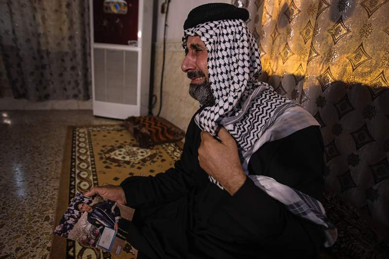 FILE - In this July 29, 2020 file photo, Jasb Hattab Aboud, father of the kidnapped protester Ali Jasb, cries as he holds his son's picture in his home un the town of Amara,Iraq.   Aboud was shot to death Wednesday, March 10, 2021, a human rights monitor and security officials said. Jasb Hattab Aboud died of a gunshot wound to the head at 6 p.m. in the southern city of Amara, said Ali al-Bayati, a spokesman for the semi-official Independent Human Rights Commission and a security official. (AP Photo/Nabil al-Jurani)
