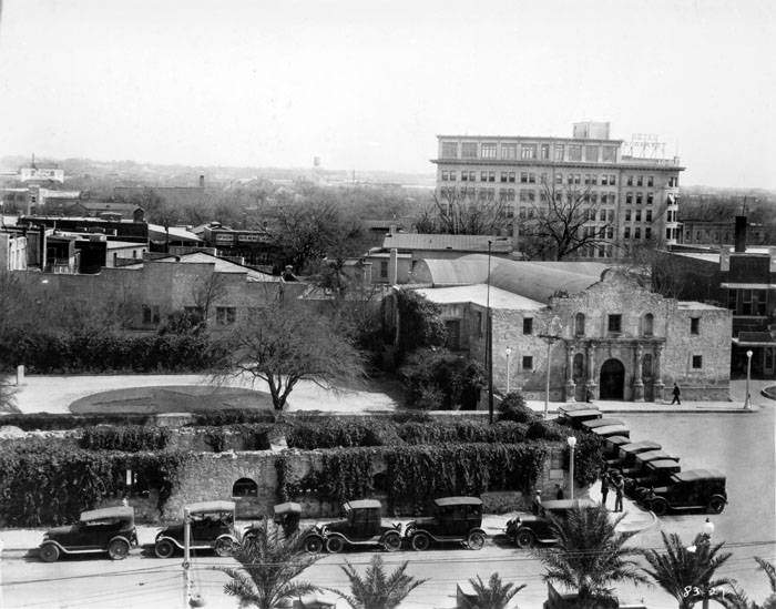Photograph shows the Alamo, Long Barrack (left) and Chapel (right).  Crockett Hotel in background (right). Photo ca. 1927.