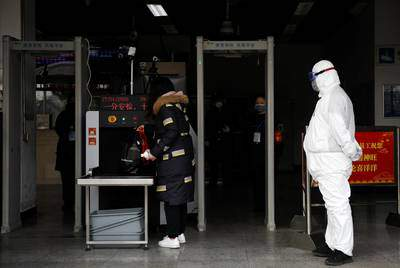 As the country is hit by an outbreak of the new coronavirus, a worker in protective suit looks on as a woman enters the Xizhimen subway station in Beijing, China on Jan. 27, 2020.      REUTERS/Carlos Garcia Rawlins