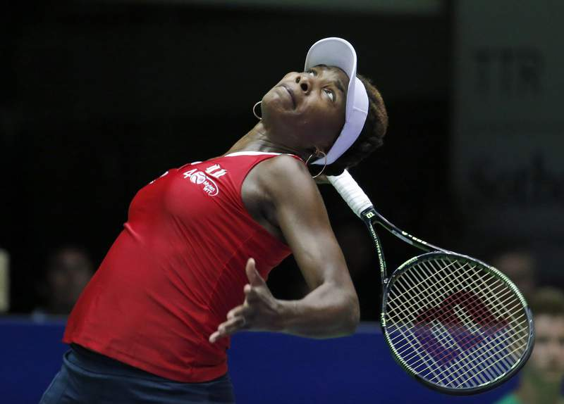 FILE - In this July 14, 2015, file photo, Washington Kastles' Venus Williams serves to Austin Aces' Nicole Gibbs during a tennis match in Washington. World TeamTennis says Venus Williams has committed to play in its three-week season that starts July 12, 2020. Williams will be a member of the Washington Kastles. That is one of nine teams that will gather at a resort in West Virginia. (AP Photo/Alex Brandon, File)