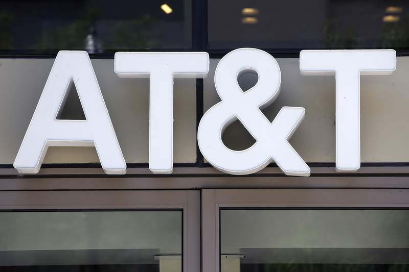 In this Monday, July 29, 2019 photo an AT&T logo sits above an entrance to a building, in Boston. As entertainment companies roll out new streaming services, they're stocking them with the goodies from their own content archives, hoping that the loss of income today will mean more money rolling in from subscribers in the future. In its fourth quarter, AT&T said that bet cost it $1.2 billion in revenue. (AP Photo/Steven Senne)