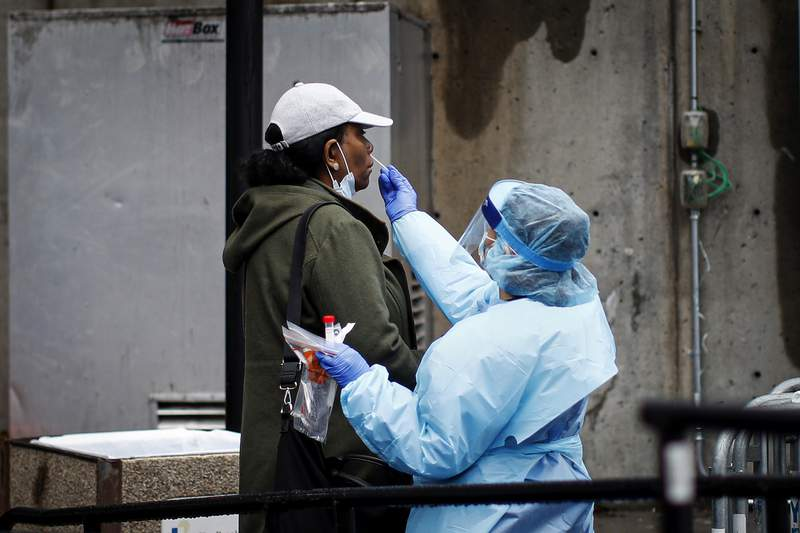 A patient is given a COVID-19 test by a medical worker outside Brooklyn Hospital Center, Sunday, March 29, 2020, in Brooklyn borough of New York. The new coronavirus causes mild or moderate symptoms for most people, but for some, especially older adults and people with existing health problems, it can cause more severe illness or death. (AP Photo/John Minchillo)