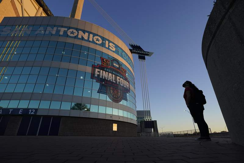 FILE - A visitor looks up at the logo for the Women's Final Four in San Antonio, as the city prepares to host the Women's NCAA College Basketball Championship, in this March 18, 2021, file photo. A law firm hired to investigate gender equity concerns at NCAA championship events released a blistering report Tuesday, Aug. 3, 2021, that recommended holding the men's and women's Final Fours at the same site and offering financial incentives to schools to improve their women's basketball programs. (AP Photo/Eric Gay, File)
