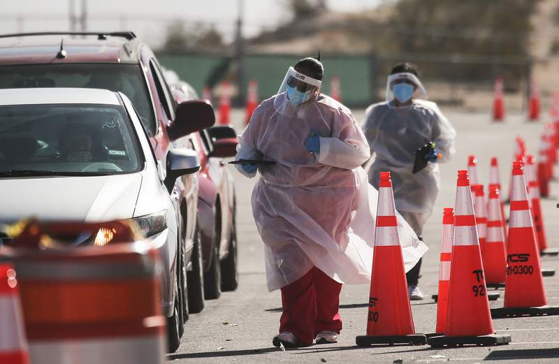 EL PASO, TEXAS - NOVEMBER 14: Frontline healthcare workers greet incoming vehicles at a drive-in COVID-19 testing site amid a surge of COVID-19 cases on November 14, 2020 in El Paso, Texas. Texas eclipsed one million COVID-19 cases November 11th with El Paso holding the most cases statewide. Health officials in El Paso today announced 15 additional COVID-19 related deaths pushing the virus death toll to 756. Active cases in El Paso are now over 30,000. (Photo by Mario Tama/Getty Images)