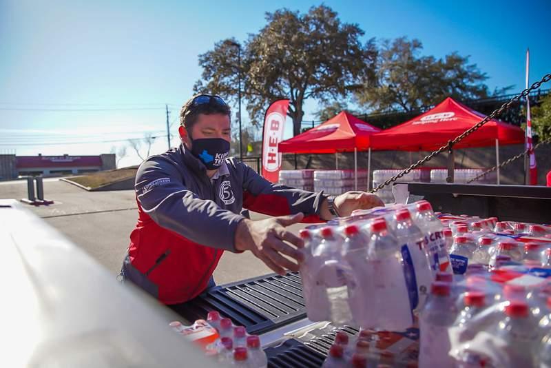 H-E-B partner loads bottled water onto the bed of a pickup truck. Courtesy: H-E-B.
