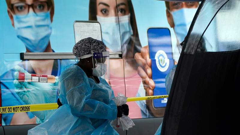 A health care employee works at a walk-up COVID-19 testing site in Miami.