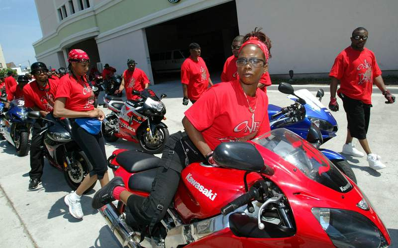 FILE - In this May 27, 2005, file photo Janine Bivens, front, mounts her sport motorcycle for a ride with her friends in Myrtle Beach, S.C. The beach town in South Carolina is in the second week of a federal trial over whether it discriminates against thousands of Black tourists who visit every May to celebrate motorcycle culture. (AP Photo/Willis Glassgow, File)