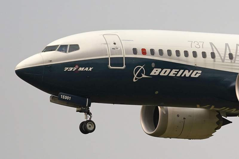 FILE- In this Sept. 30, 202, file photo, a Boeing 737 Max jet, piloted by Federal Aviation Administration (FAA) chief Steve Dickson, prepares to land at Boeing Field following a test flight in Seattle.  (AP Photo/Elaine Thompson, File)