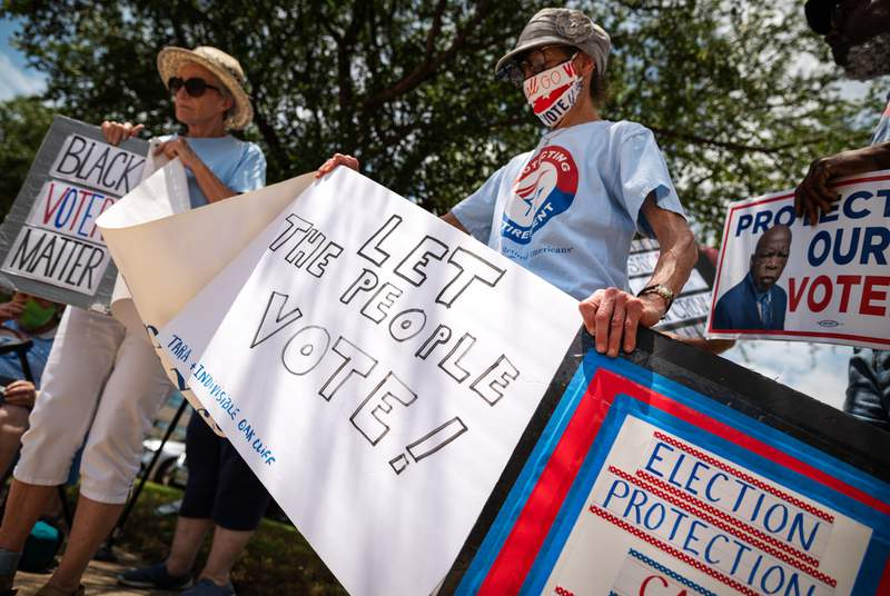 From left: Louise Calvillo and Charolette Connelly, members of the Texas Alliance for Retired Americans (TARA), hold a variety of signs as they protest against voter suppression outside of the office of State Rep. Angie Chen Button, R-Richardson, in Richardson on June 24, 2021.