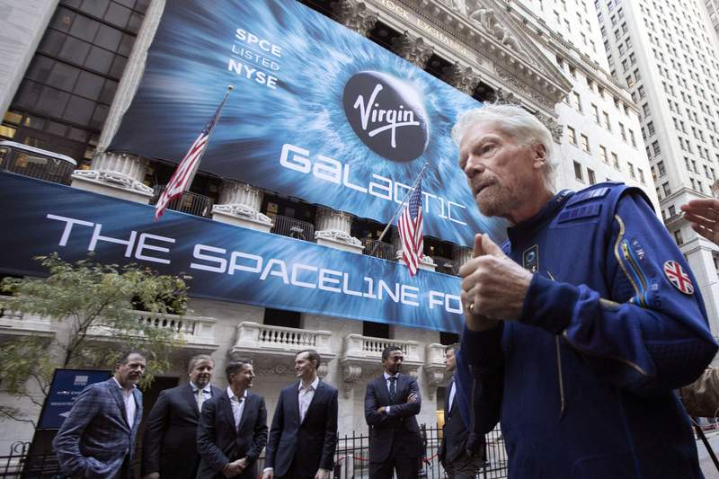 FILE - In this Monday, Oct. 28, 2019 file photo, Richard Branson, right, founder of Virgin Galactic, and company executives gather for photos outside the New York Stock Exchange before his company's IPO. In an interview after the Wednesday, June 30, 2021 satellite launch by his separate company Virgin Orbit, Branson said that he has to be so circumspect in what he says about Virgin Galactic. All I can say is when the engineers tell me that I can go to space, Im ready, fit and healthy to go. So well see, he said. (AP Photo/Richard Drew, File)