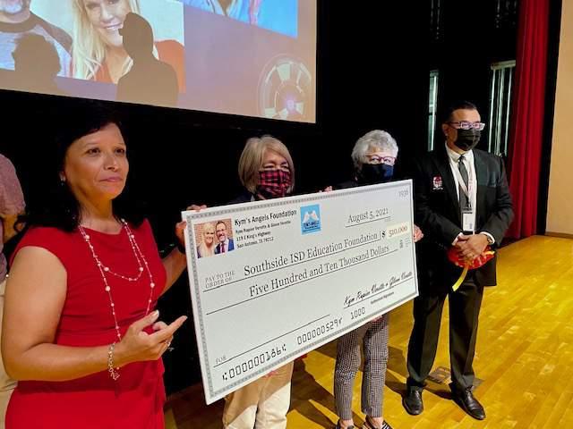 Kym's Angels spokeswoman Yolanda Valenzuela presents a check for $510,000 to Southside ISD Superintendent Mr. Rolando Ramirez and district board members Mary Silva, center, and Velia Minjarez.