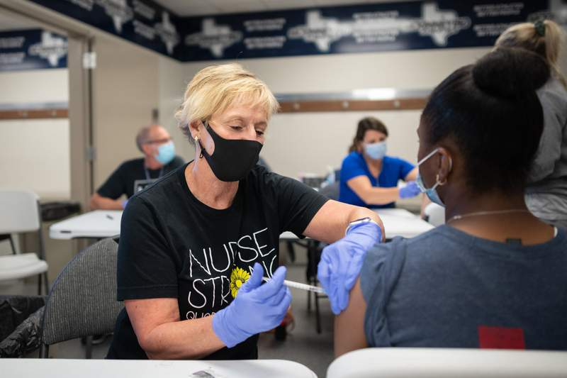 McKinney ISD registered nurse Nancy Yarbrough administers a COVID-19 vaccine to a student at McKinney ISD Stadium and Community Event Center in on May 20, 2021.