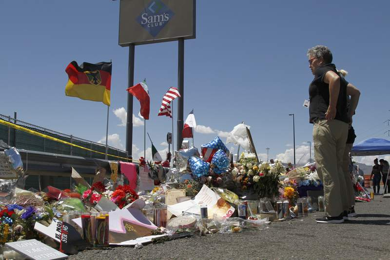 FILE - In this Aug. 12, 2019 photo, mourners visit the makeshift memorial near the Walmart in El Paso, Texas, where 22 people were killed in a mass shooting.  Officials in the border city are unveiling a garden meant to bring healing two years after a gunman targeting Latinos opened fire, ultimately killing 23 people in an attack that stunned the U.S. and Mexico.   (AP Photo/Cedar Attanasio, File)