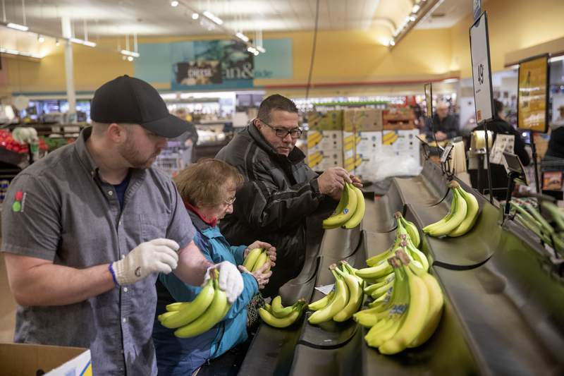 Nancy Pesapand, 92, center, grabs bananas as a worker restocks the produce section of a Stop & Shop supermarket during hours open daily only for seniors Thursday, March 19, 2020, in North Providence, R.I. This week grocery store chains and other retailers began offering special shopping hours for seniors and other groups considered the most vulnerable to the new coronavirus. The dedicated shopping times are designed to allow seniors, pregnant women and people with underlying health conditions to shop among smaller crowds and reduce their chances of acquiring the virus. (AP Photo/David Goldman)
