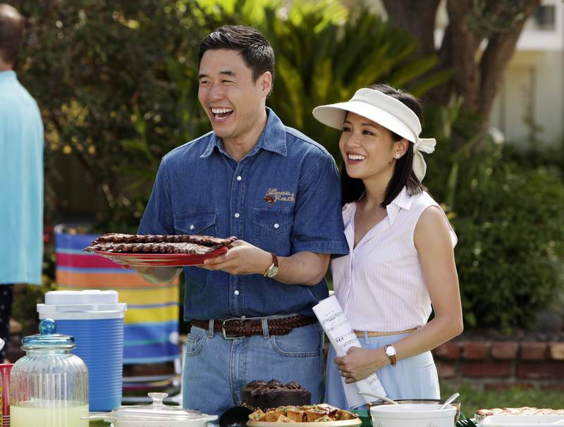 """In this image released by ABC, Randall Park, left, and Constance Wu appear in a scene from the new comedy series """"Fresh Off the Boat."""" The all-Asian casts of Fresh Off the Boat and Canadian sitcom Kims Convenience are partnering for one night for charity. In honor of Asian Pacific American Heritage Month, the stars of both TV comedies will do live online table reads of their respective pilot episodes on Saturday, according to Deadline. (Nicole Wilder/ABC via AP)"""