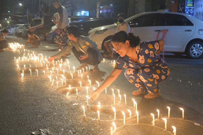 People light candles on the street during a night demonstration despite a curfew imposed by authorities in Yangon, Myanmar on Friday, Mar. 12, 2021. Police in Myanmar fired rubber bullets and tear gas at protesters in the country's two largest cities and elsewhere on Friday, as authorities continued their harsh crackdown on opponents of last month's military coup. (AP Photo)