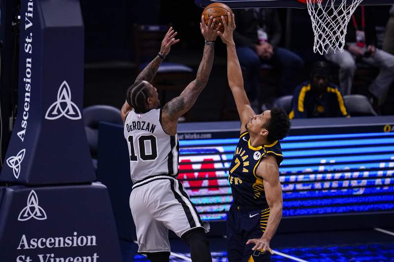 Indiana Pacers guard Malcolm Brogdon, right, blocks the shot of San Antonio Spurs forward DeMar DeRozan, left, during the first half of an NBA basketball game in Indianapolis, Monday, April 19, 2021. (AP Photo/Michael Conroy)