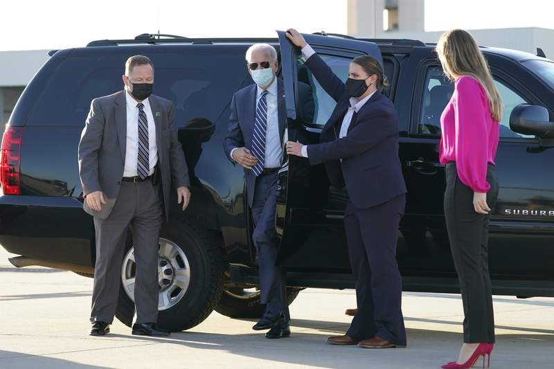 In this Oct. 18, 2020, photo, Democratic presidential candidate former Vice President Joe Biden steps out to board his campaign plane at Raleigh-Durham International Airport in Morrisville, N.C., en route to Wilmington, Del., as granddaughter Finnegan Biden looks on, right. Biden's biggest challenge may begin the day after Election Day. If he wins, he'll have just over 10 weeks to set up a new government. After making President Donald Trumps handling of the coronavirus pandemic a centerpiece of his campaign, Biden will have to show that his team can better handle the public health crisis.  (AP Photo/Carolyn Kaster)