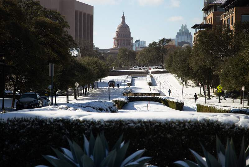 Snow covers the roadways along Brazos St. near the University of Texas campus in Austin on Feb. 15, 2021.