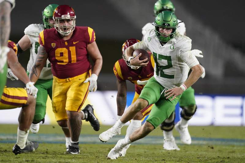 Oregon quarterback Tyler Shough (12) runs the ball during the second half of an NCAA college football game for the Pac-12 Conference championship against Southern California Friday, Dec 18, 2020, in Los Angeles. (AP Photo/Ashley Landis)