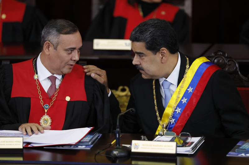 FILE - In this Jan. 31, 2020 file photo, Venezuelan President Nicolas Maduro, right, speaks with Supreme Court President Maikel Moreno at the Supreme Court in Caracas, Venezuela. Maduro is at the court to give his annual presidential address.  On Thursday, March 26, 2020, the U.S. Justice Department made public it has charged in several indictments against Maduro and his inner circle, including Moreno, that the leader has effectively converted Venezuela into a criminal enterprise at the service of drug traffickers and terrorist groups as he and his allies stole billions from the South American country. (AP Photo/Ariana Cubillos, File)