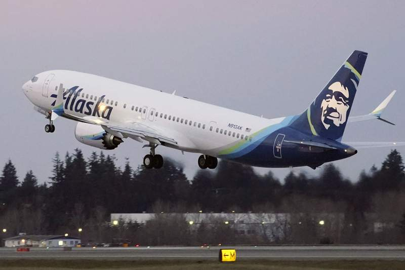 FILE - In this Monday, March 1, 2021 file photo, The first Alaska Airlines passenger flight on a Boeing 737-9 Max airplane takes off on a flight to San Diego from Seattle-Tacoma International Airport in Seattle. A Boeing pilot involved in testing the 737 Max jetliner was indicted Thursday, Oct. 14,2021 by a federal grand jury on charges of deceiving safety regulators who were evaluating the plane, which was later involved in two deadly crashes. (AP Photo/Ted S. Warren, File)