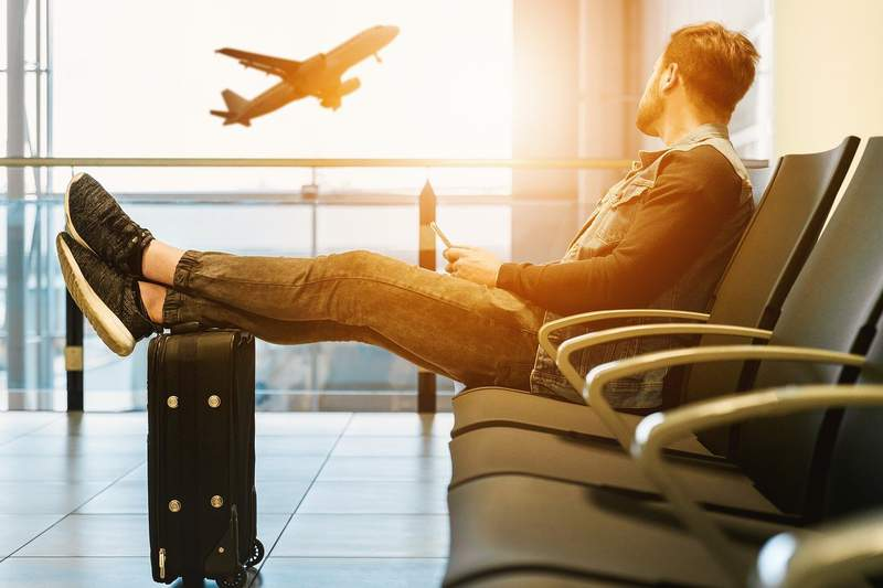 A man sits alone at an airport gate.