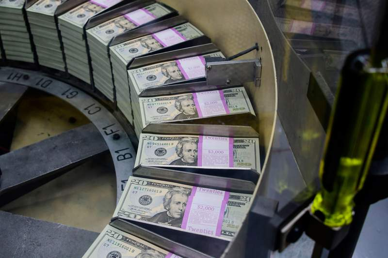Packs of freshly printed 20 USD notes are processed for bundling and packaging at the US Treasury's Bureau of Engraving and Printing in Washington, DC July 20, 2018. - The dollar slid against the euro and pound on Friday, July 20, 2018, as US President Donald Trump adopted an aggressive posture on trade and foreign exchange, stoking talk of a currency war in addition to a trade war. (Photo by Eva HAMBACH / AFP)        (Photo credit should read EVA HAMBACH/AFP via Getty Images)