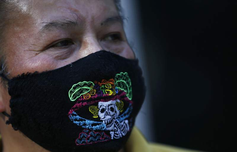 """Pedro Nuez wears a mask embroidered with the image of a """"catrina"""" during the COVID-19 pandemic as he waits for clients at his kiosk where he sells sweets and soft drinks on Paseo de la Reforma in Mexico City, Monday, Jan. 25, 2021. (AP Photo/Marco Ugarte)"""